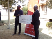 The Marketing Director (left) of Airtel Malawi ceremonially presenting a cheque to the Chairman of COSOMA Board